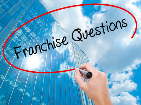 Man Hand writing Franchise Questions with black marker on visual screen. Business, technology, internet concept. Modern business skyscrapers background. Stock Photo