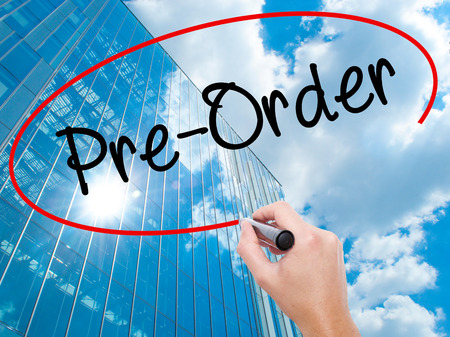 Man Hand writing Pre-Order  with black marker on visual screen.  Business, technology, internet concept. Modern business skyscrapers background. Stock Photo