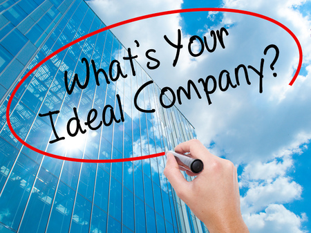 Man Hand writing Whats Your Ideal Company? with black marker on visual screen.  Business, technology, internet concept. Modern business skyscrapers background. Stock Photo