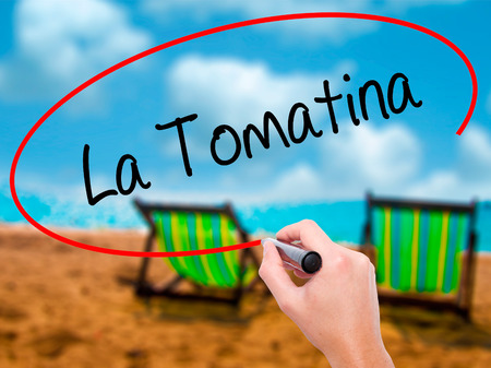 Man Hand writing La Tomatina with black marker on visual screen. Isolated on sunbed on the beach. Business, technology, internet concept.