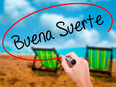 Man Hand writing Buena Suerte( Good Luck in Spanish) with black marker on visual screen. Isolated on sunbed on the beach. Business, technology, internet concept. Stock Photo