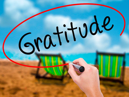 Man Hand writing Gratitude with black marker on visual screen. Isolated on sunbed on the beach. Business, technology, internet concept. Stock Photo