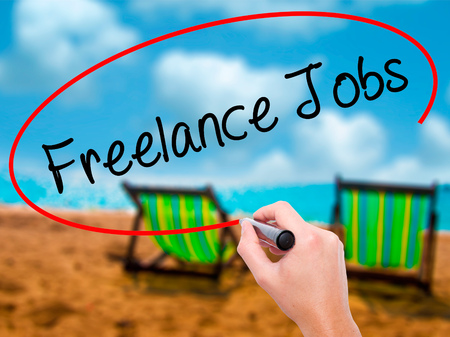 Man Hand writing Freelance Jobs with black marker on visual screen. Isolated on sunbed on the beach. Business, technology, internet concept. Stock Photo