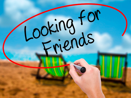Man Hand writing Looking for Friends with black marker on visual screen. Isolated on sunbed on the beach. Business, technology, internet concept. Stock Photo