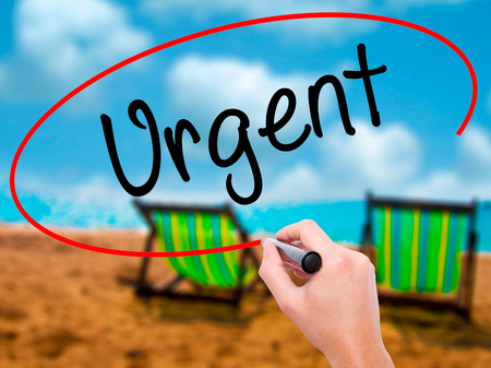 Man Hand writing Urgent  with black marker on visual screen. Isolated on sunbed on the beach. Business, technology, internet concept. Stock Photo