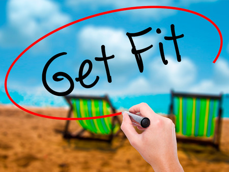 Man Hand writing Get Fit  with black marker on visual screen. Isolated on sunbed on the beach. Business, technology, internet concept. Stock Photo