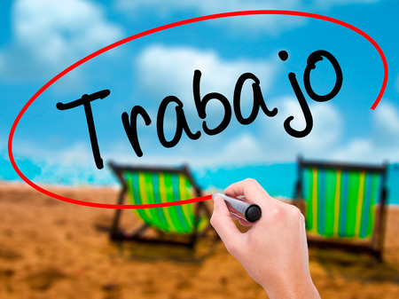 Man Hand writing Trabajo  ( work in Spanish) with black marker on visual screen. Isolated on sunbed on the beach. Business, technology, internet concept. Stock Photo