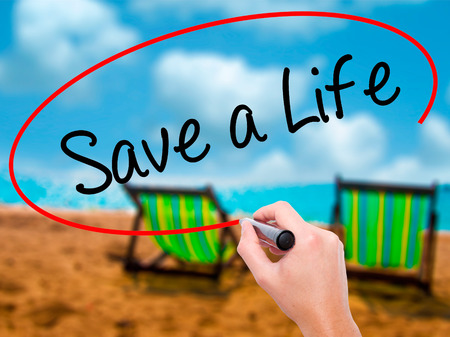 Man Hand writing Save a Life  with black marker on visual screen. Isolated on sunbed on the beach. Business, technology, internet concept. Stock Photo