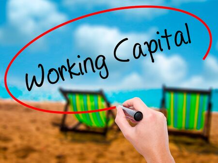 Man Hand writing Working Capital with black marker on visual screen. Isolated on sunbed on the beach. Business, technology, internet concept. Stock Photo