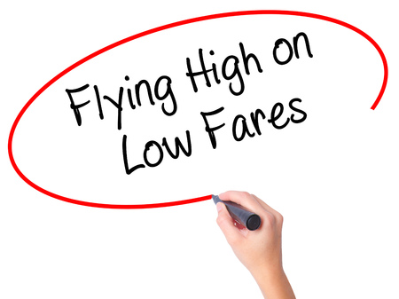 Women Hand writing Flying High on Low Fares with black marker on visual screen. Isolated on white. Business, technology, internet concept. Stock Photo