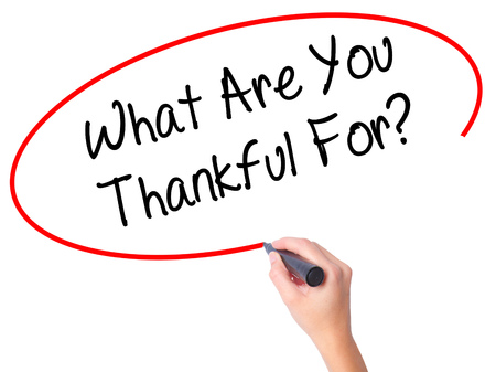 Women Hand writing What Are You Thankful For? with black marker on visual screen. Isolated on white. Business, technology, internet concept.