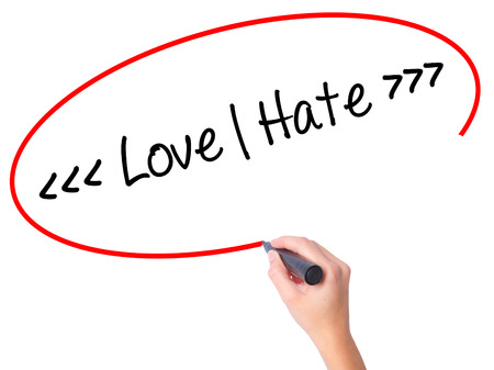 Women Hand writing Love - Hate  with black marker on visual screen. Isolated on white. Business, technology, internet concept. Stock Photo