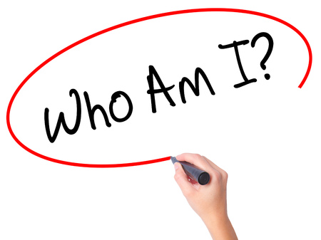 Women Hand writing Who Am I? with black marker on visual screen. Isolated on white. Business, technology, internet concept. Stock Photo