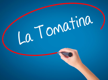 Women Hand writing La Tomatina with black marker on visual screen. Isolated on blue. Business, technology, internet concept.