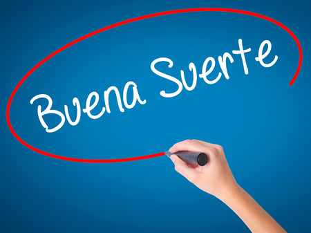 Women Hand writing Buena Suerte( Good Luck in Spanish) with black marker on visual screen. Isolated on blue. Business, technology, internet concept. Stock Photo
