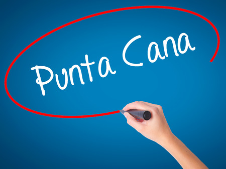 Women Hand writing Punta Cana with black marker on visual screen. Isolated on blue. Business, technology, internet concept. Stock Photo