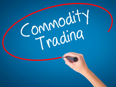 Women Hand writing Commodity Trading with black marker on visual screen. Isolated on blue. Business, technology, internet concept. Stock Photo