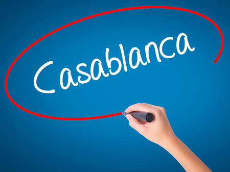 Women Hand writing Casablanca with black marker on visual screen. Isolated on blue. Business, technology, internet concept. Stock Photo