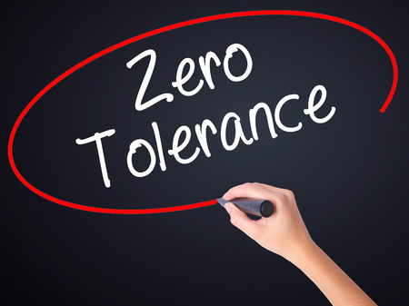 Woman Hand Writing Zero Tolerance on blank transparent board with a marker isolated over black background. Stock Photo
