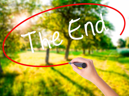 Woman Hand Writing The End on blank transparent board with a marker isolated over green field background. Business concept. Stock Photo