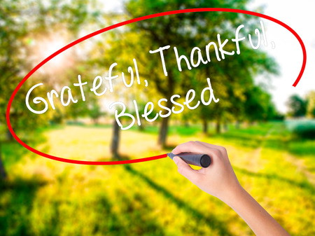 Woman Hand Writing  Grateful Thankful Blessed on blank transparent board with a marker isolated over green field background. Stock Photo