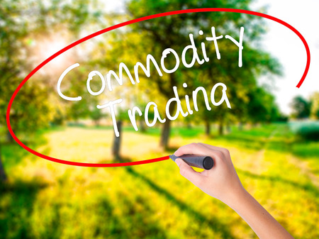 Woman Hand Writing Commodity Trading on blank transparent board with a marker isolated over green field background. Stock Photo