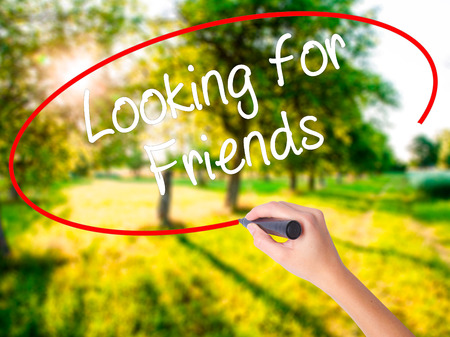 Woman Hand Writing Looking for Friends on blank transparent board with a marker isolated over green field background. Stock Photo