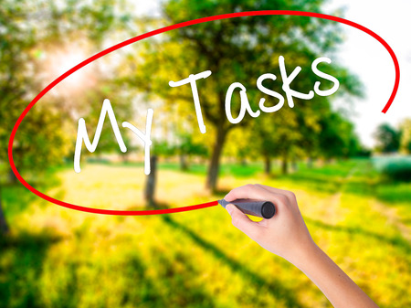 Woman Hand Writing My Tasks on blank transparent board with a marker isolated over green field background. Stock Photo