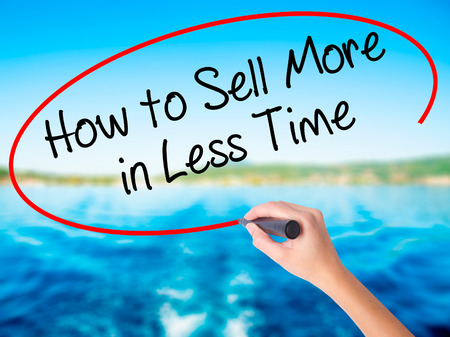 Woman Hand Writing How to Sell More in Less Time on blank transparent board with a marker isolated over water background. Business concept. Stock Photo