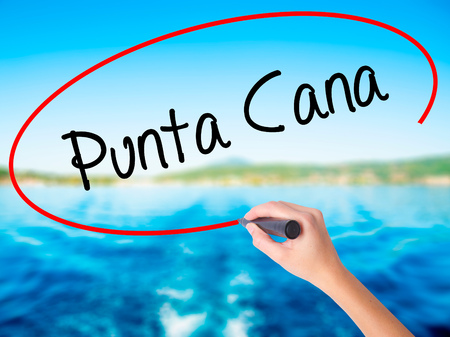 Woman Hand Writing Punta Cana on blank transparent board with a marker isolated over water background. Business concept. Stock Photo