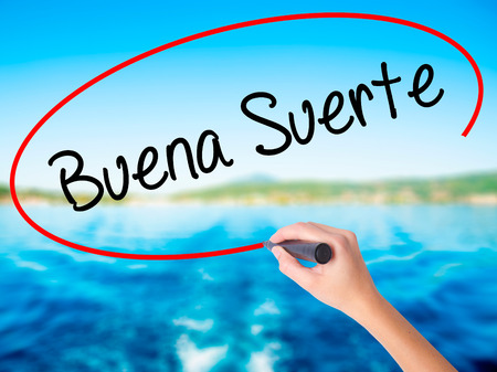 Woman Hand Writing Buena Suerte( Good Luck in Spanish) on blank transparent board with a marker isolated over water background. Business concept. Stock Photo