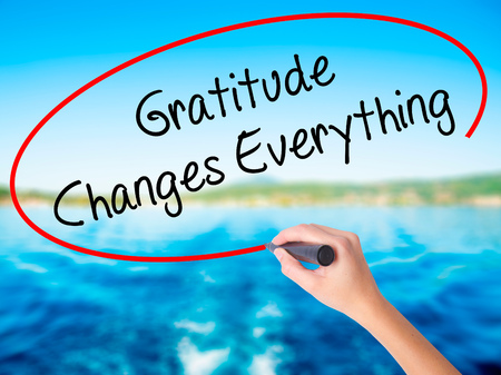 Woman Hand Writing Gratitude Changes Everything on blank transparent board with a marker isolated over water background. Business concept. Stock Photo