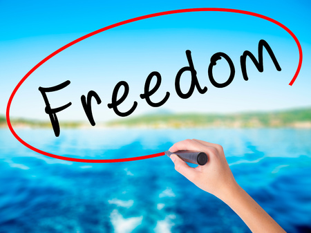 Woman Hand Writing Freedom on blank transparent board with a marker isolated over water background. Business concept. Stock Photo