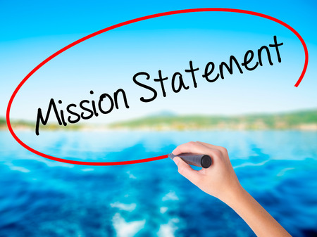 Photo pour Woman Hand Writing Mission Statement on blank transparent board with a marker isolated over water background. Business concept. Stock Photo - image libre de droit