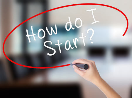 Woman Hand Writing How do I Start? with a marker over transparent board. Isolated on Office. Learn, technology, internet concept. Stock Image