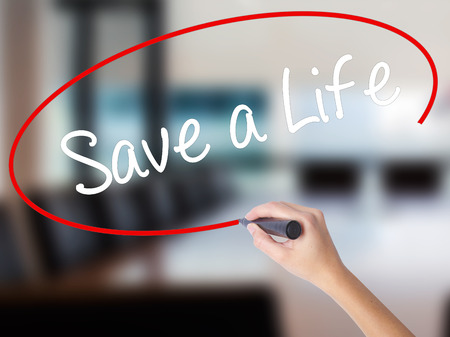 Woman Hand Writing Save a Life  with a marker over transparent board. Isolated on Office. Business concept. Stock Photo