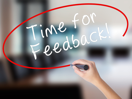 Woman Hand Writing Time for Feedback with a marker over transparent board. Isolated on Office. Business concept. Stock Image