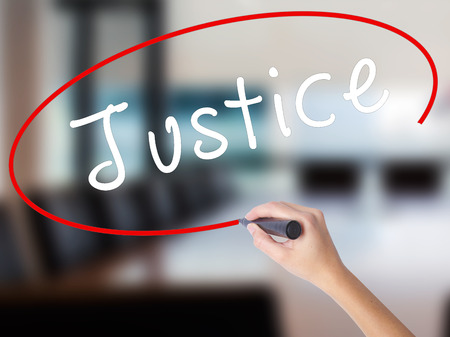 Woman Hand Writing Justice with a marker over transparent board. Isolated on Office. Business concept. Stock Image