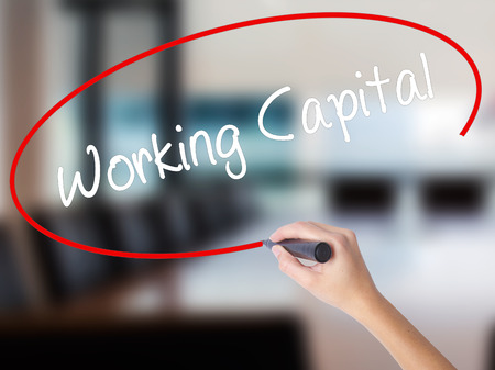 Woman Hand Writing Working Capital with a marker over transparent board. Isolated on Office. Business concept. Stock Photo