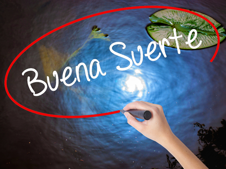 Woman Hand Writing Buena Suerte( Good Luck in Spanish) with marker over transparent board. Isolated on nature. Business concept. Stock Photo