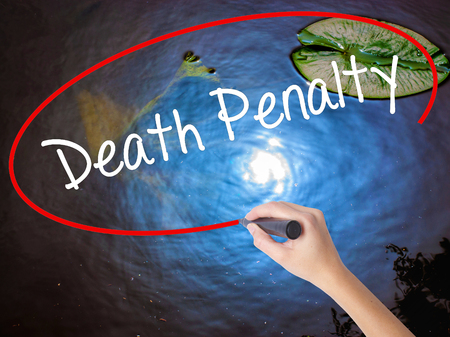 Woman Hand Writing Death Penalty with marker over transparent board. Isolated on nature. Business concept. Stock Photo