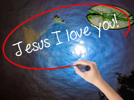 Woman Hand Writing Jesus I love you! with marker over transparent board. Isolated on nature. Business concept. Stock Photo