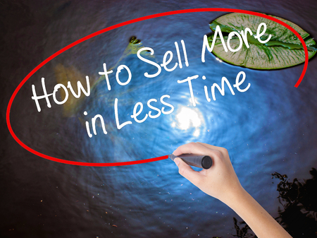 Woman Hand Writing How to Sell More in Less Time with marker over transparent board. Isolated on nature. Business concept. Stock Photo