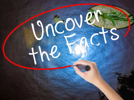 Woman Hand Writing Uncover the Facts with marker over transparent board. Isolated on nature. Business concept. Stock Image