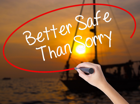 Woman Hand Writing Better Safe Than Sorry with a marker over transparent board. Isolated on Sunset Boat. Business concept. Stock Photo