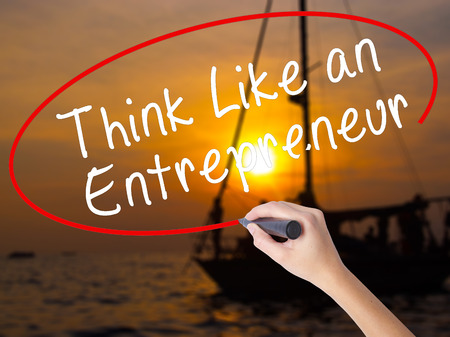 Woman Hand Writing Think Like an Entrepreneur with a marker over transparent board. Isolated on Sunset Boat. Business, technology, internet concept. Stock Image