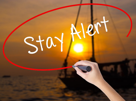 Woman Hand Writing Stay Alert with a marker over transparent board. Isolated on Sunset Boat. Business concept. Stock Photo