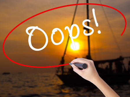 Woman Hand Writing Oops! with a marker over transparent board. Isolated on Sunset Boat. Business, technology, internet concept. Stock Image