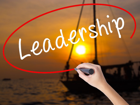 Woman Hand Writing Leadership with a marker over transparent board. Isolated on Sunset Boat. Business, technology, internet concept. Stock Image