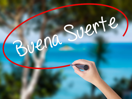 Woman Hand Writing Buena Suerte( Good Luck in Spanish) with black marker on visual screen. Isolated on nature. Business concept. Stock Photo